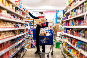 Full shopping cart, customer is stocking vital needs because of global chaos. Shopping with blur supermarket store products, interior background.