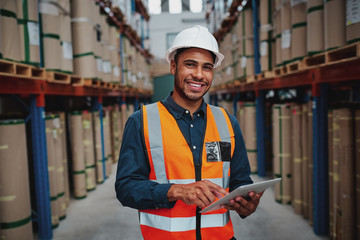 Happy male factory manager using digital tablet in warehouse while standing against goods shelf looking at camera