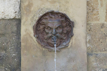 gargoyle spitting water at a well in Pitigliano