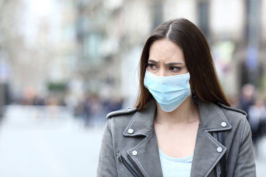 Scared woman with protective mask avoiding contagion on street