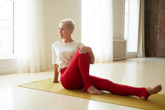 Beautiful mature woman with gray pixie hair and athletic body sitting on mat turning torso to side with one knee bent, doing stretching exercises during morning yoga, having energetic look