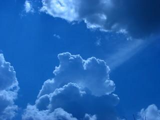 Fototapeta błękitne, niebieskie niebo rozświetlone promieniami słońca  obraz