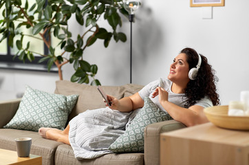 technology, people and leisure concept - happy young woman in headphones listening to music on smartphone at home
