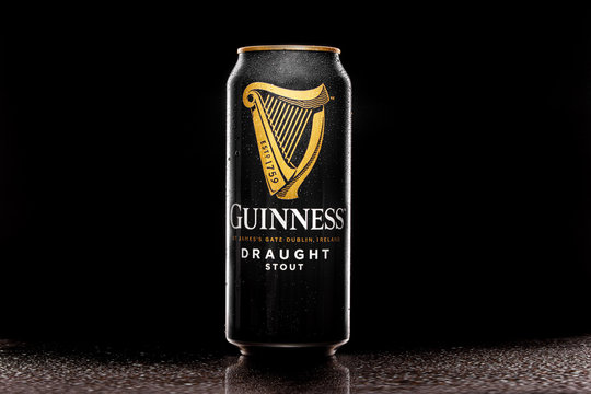 MINSK, BELARUS - March 16, 2020: Close-up Guinness draught, the popular Irish beer, in a can on a black background with water drops.
