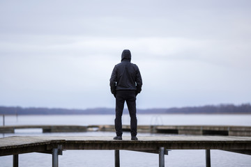 One young man in black clothes standing alone on wooden footbridge and staring at lake. Hooded guy. Peaceful atmosphere in nature. Enjoying fresh air in winter. Back view. Fotobehang