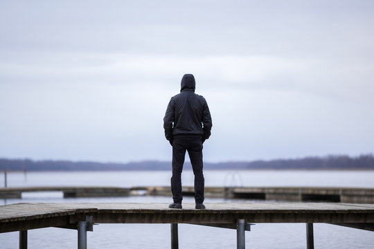 One young man in black clothes standing alone on wooden footbridge and staring at lake. Hooded guy. Peaceful atmosphere in nature. Enjoying fresh air in winter. Back view.