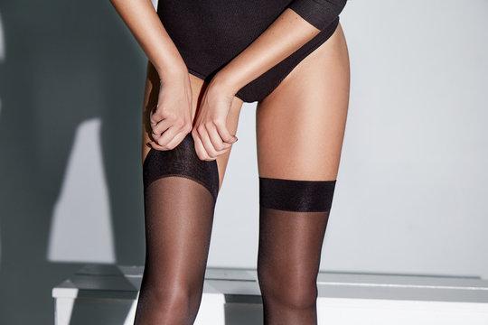 Part of woman body perfect shape hips legs skin tan wear stockings, nylons, pantyhose lingerie hosiery hose studio shot. on white background high heels romantic.