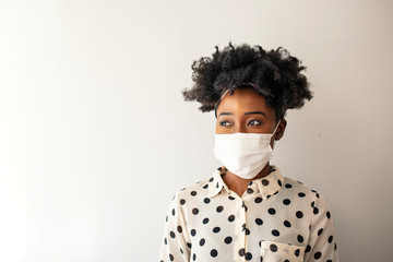 Masked woman - protection against influenza virus. African - American woman wearing mask for...