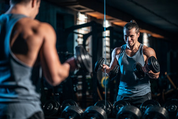 young athlete has physical workout with dumbbell in modern gym