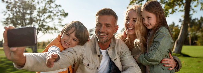 Lets make our portrait. Happy family taking selfies outdoors