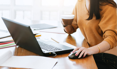 Business woman using laptop for working or learning  and holding coffee cup to drink