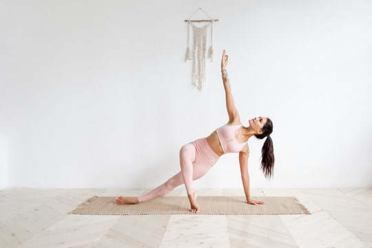 Young attractive woman practicing yoga in bright yoga class on wooden eco floors tanding in Full Version of Vasisthasana exercise, Side Plank pose, working out, pink sportswear. White wall background