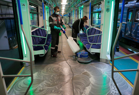 Employees wearing protective face masks clean and disinfect a subway train in Moscow