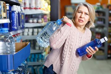 Tense adult woman lifting heavy bottle water