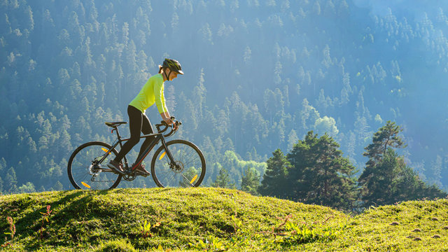 A young smiling woman on a cyclocross bike rides against the background of a green forest on a sunlit meadow