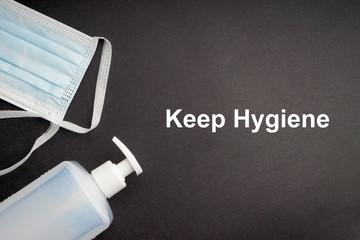 KEEP HYGIENE text antibacterial soap sanitizer and protective face mask on black background. Covid-19 or Coronavirus Concept