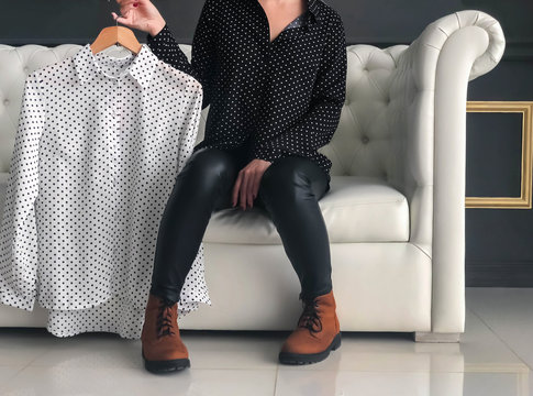 A girl in black leather trousers and suede boots demonstrates a white blouse with black polka dots