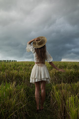 Carefree woman wearing straw hat in the rice field