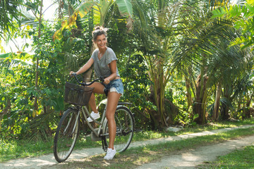 Sexy and beautiful woman with  a bicycle in the tropical garden