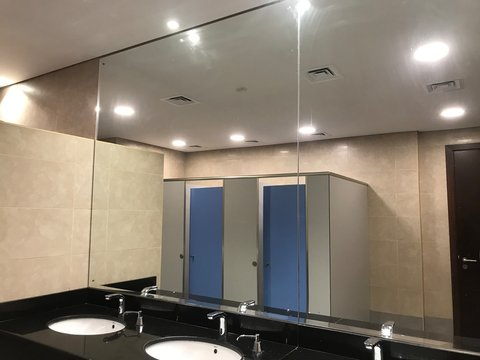 Big mirror image of toilet cubicles of an Men washroom and wash basin counter finished with polished black granite finishes fixed with chrome plated spouts and soap dispenser for washing hands