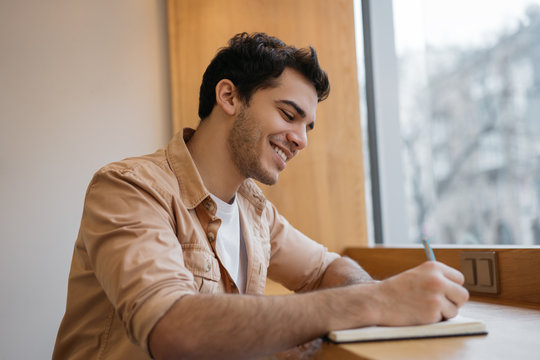 Happy Indian business man writing on notebook, working project, planning strategy in office. Smiling university student studying, exam preparation, taking notes. Education concept