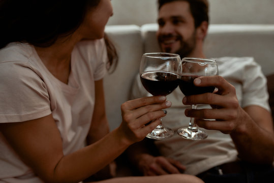 Cheers. Happy couple relaxing, drinking wine and talking while sitting on couch at home