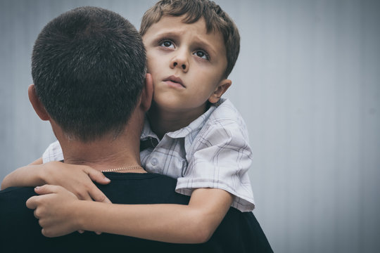 Portrait of young sad little boy and father standing outdoors at the day time.