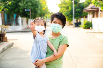 Asian beautiful mother carrying her little daughter wearing protection mask in covid 19 or corona virus outbreak situation before going to school, Covid 19 or Corona virus outbreak concept
