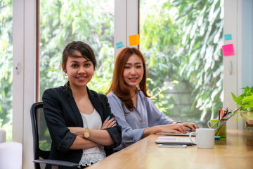 Portrait of businesswoman and her colleague working together in modern office building, Business concept