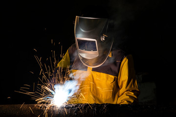 Worker welding a part of construction steel in his workshop, Welding and construction concept