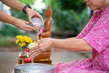 Thai woman pour water on the hands of revered elders or her grand parent for doing respected and ask for blessing in Thai Songkran festival, a famous cultural day in Thailand, Asian family Concept