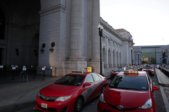 Long lines of taxis wait for very few commuters as they transit through Union Station, normally a busy transportation and commuter hub, during rush hour in Washington