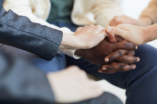 Close up of people holding hands while comforting each other in psychology support group, copy space