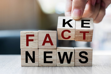 Businessman hand holding wooden cube with flip block FAKE to FACT News word on table background. News, solution and business  concepts