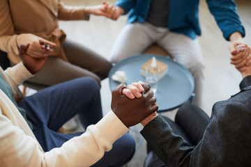 High angle closeup of multi-ethnic group of people holding hands in prayer while sitting in circle in support group, copy space