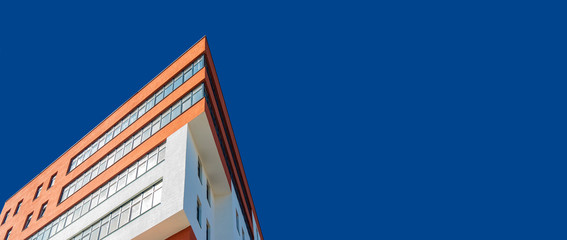 modern architecture building triangle shape panoramic urban photography concept foreshortening from below on vivid blue sky wallpaper pattern background space for copy or your text Wall mural