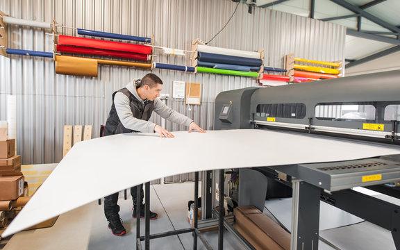 Technician operator works on large premium industrial printer plotter machine