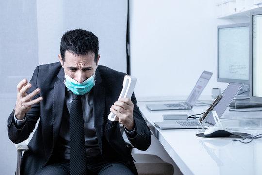 Manager in abito si protegge con una mascherina e discute al telefono seduto nella poltrona della sua scrivania