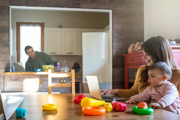 Family at home in the kitchen, mom works at the computer at the table with her daughter on her legs while playing with toys, the father cooks lunch - Millennials in an intimate moment with their child