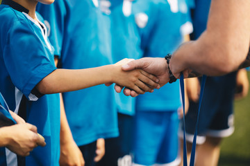 Soccer handshake during ceremony. Kids getting awarded with golden medals after school tournament. Child and adult handshaking