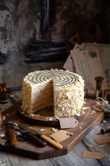 traditional hungarian cut esterhazy cake on wooden boards on grey wooden table with copper cups, vintage forks, almond flakes opposite concrete wall