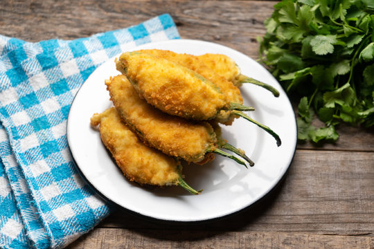 Mexican jalapeno poppers stuffed with cheese and breaded on wooden background