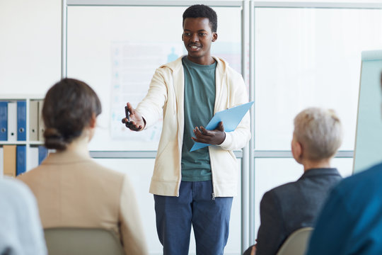 Portrait of young African-American man giving speech during meeting with audience, copy space