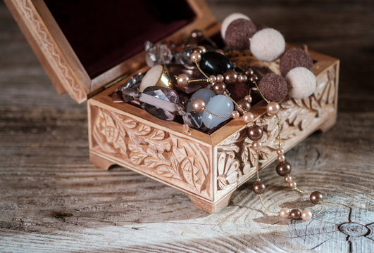 wooden vintage jewelry box with jewelry on a wooden background