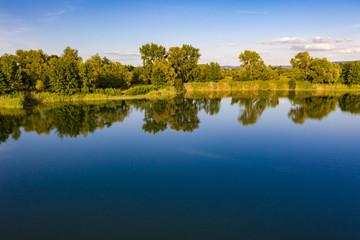 Eine Luftaufnahme mit grünen Bäumen an einem blauen See