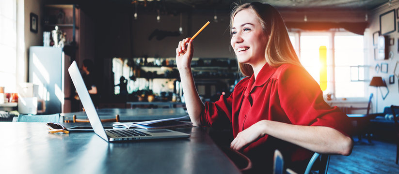 Young and smiling woman working with laptop in the morning in big spacious room