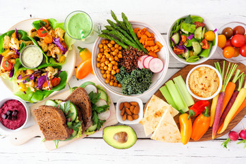 Healthy lunch table scene with nutritious lettuce wraps, Buddha bowl, vegetables, sandwiches, and salad. Overhead view over a white wood background. Fototapete