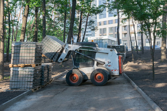 A small loader works in the park and carries piles of paving slabs. Works on improvement in the park.