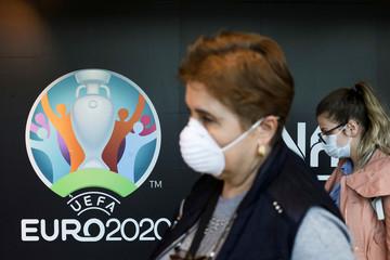 Travellers pass by a logo of the 2020 UEFA European Football Championship displayed on a wall inside Bucharest Henri Coanda International Airport