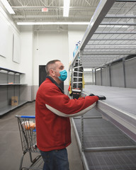 Man in Mask Looking at Empty Grocery Store Shelf